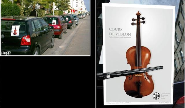 Violin flyer placed under windscreen wiper so that wiper looks like bow of violin.