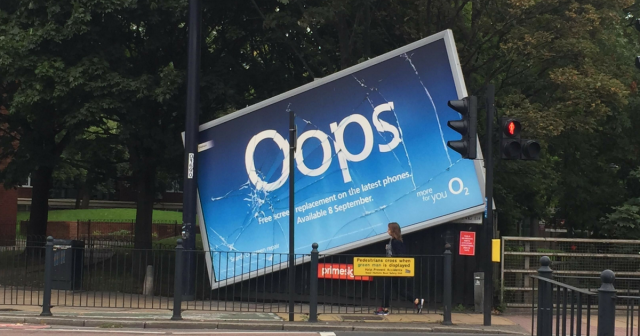 "Billboard that looks like it's fallen, shattering its glass. Ad reads ""OOPS"""