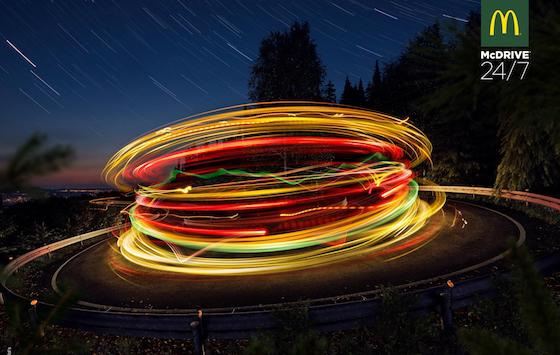 Simulated long exposure of car lights on roundabout creating impression of neon hamburger