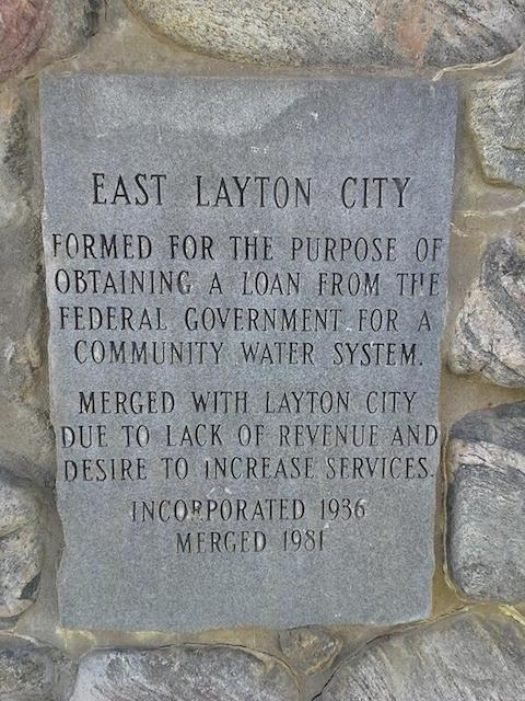 Plaque: EAST LAYTON CITY. Formed for the purpose of obtaining a a loan from the federal government for a community water system. Merged with Layton City due to lack of revenue and desire to increase services. Incorporated 1936. Merged 1981